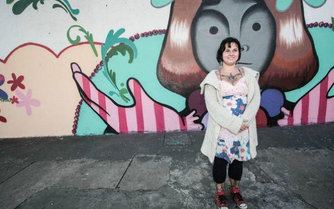 Tikka a frente de um dos muros pintados por ela